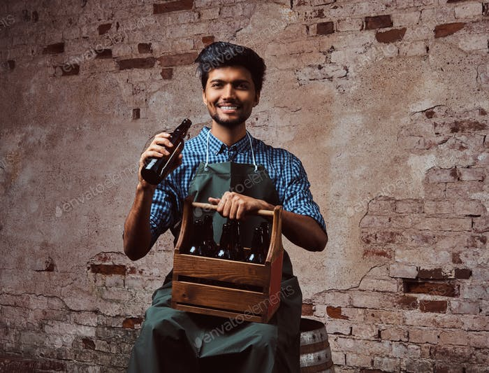 Indian brewer in uniform sitting on a wooden barrel and drink craft beer.