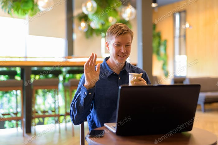 Happy young handsome businessman with coffee video calling at the coffee shop