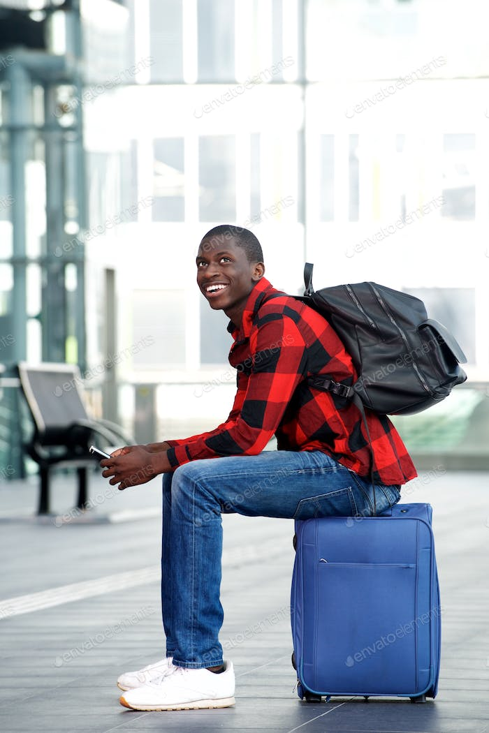 Smiling young man sitting on traveling bag with mobile phone
