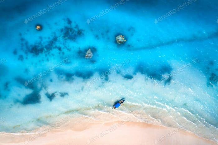 Aerial view of the fishing boat in clear blue water at sunset