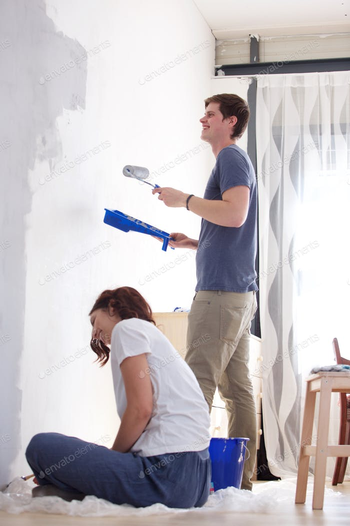 happy boyfriend and girlfriend painting wall in new house