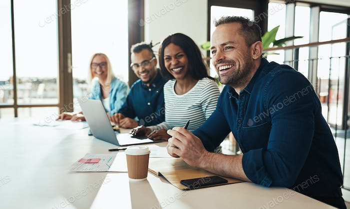 Diverse office colleagues laughing together during a meeting