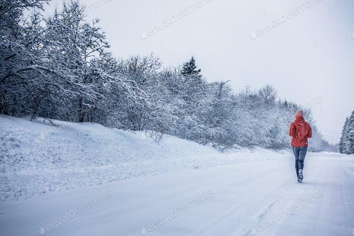 Frau läuft allein mit Bewegungsunschärfe während der kalten Schneedecke Tag der Wi