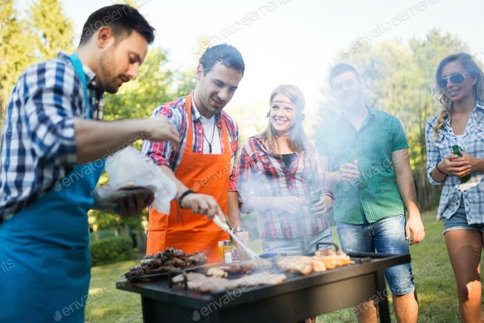 Happy friends enjoying barbecue party in nature