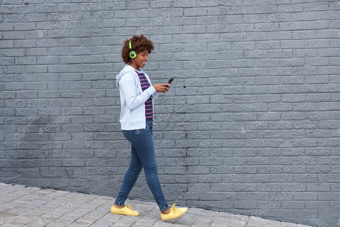 african woman walking and listening to music on mobile phone