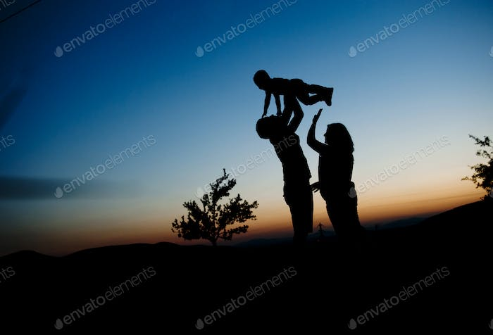 Silhouette of happy family in nature
