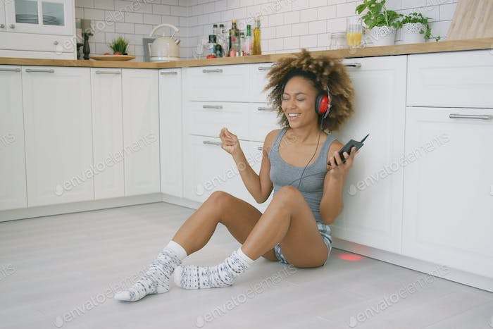 Laughing woman with gadgets in kitchen