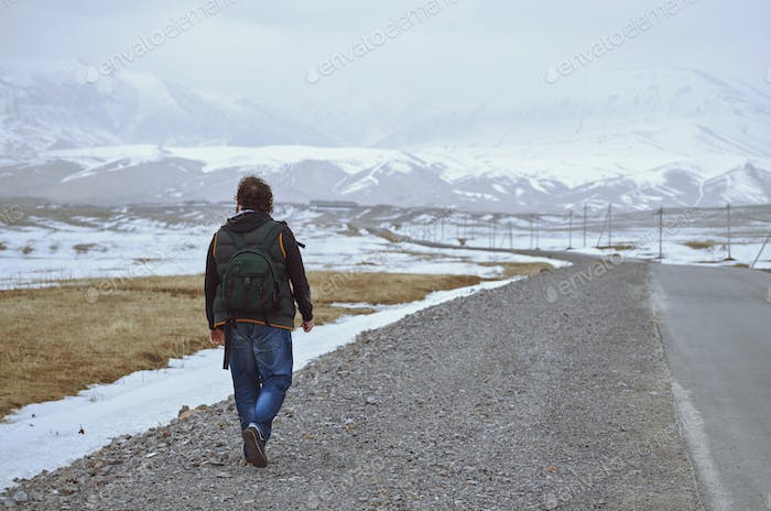 Traveller Wearing Backpack and Walking Along the Rural Highway