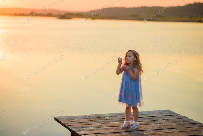 Ein kleines Mädchen bläst Blasen auf dem Pier in der Nähe des Sees.