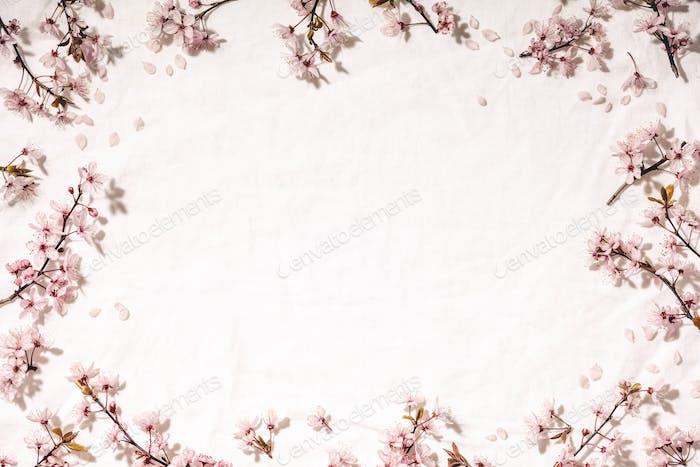Spring border with cherry blossoms on white linen napkin