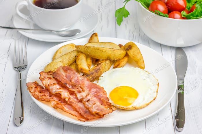Herzhaftes Frühstück mit Speck, Spiegelei, Kartoffel und Tasse Kaffee