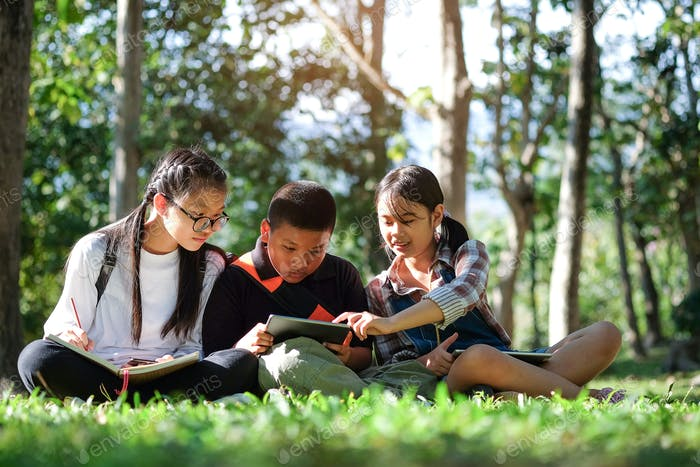 Three asian boy and girls read book in garden.