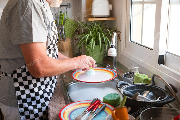 Human hands of an elderly man washing dishes. Give a hand in domestic life. Kitchen corner.