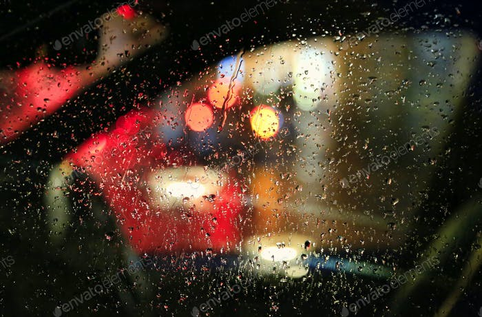 Lichter der Nacht Stadt durch das Glas des Autos mit Regentropfen