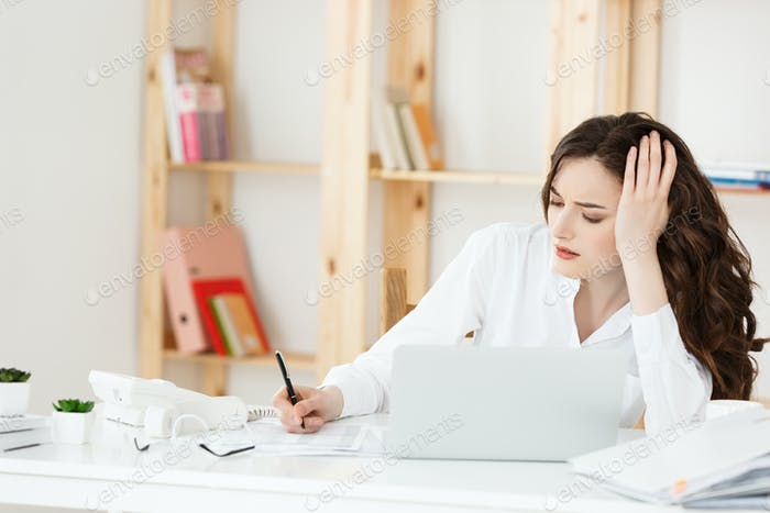Tired beautiful Businesswoman holding hand on head while working on computer and some business