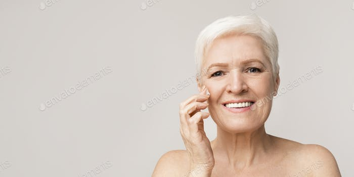 Morning routine. Elderly lady applying face cream on cheek