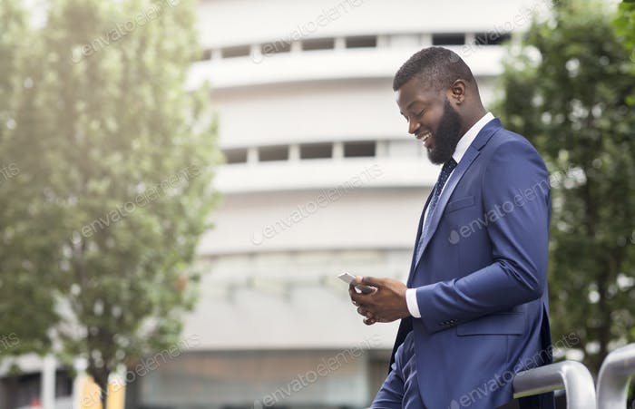 Attractive businessman texting on cellphone, standing near modern office building