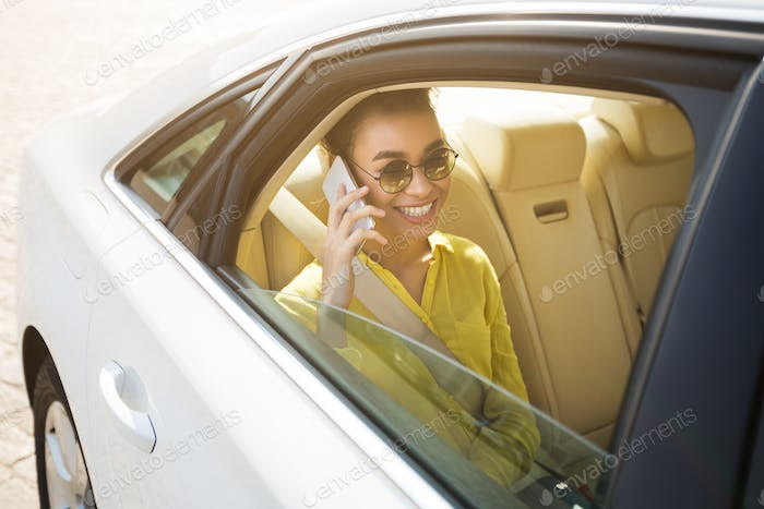 Happy afro woman talking on phone in car