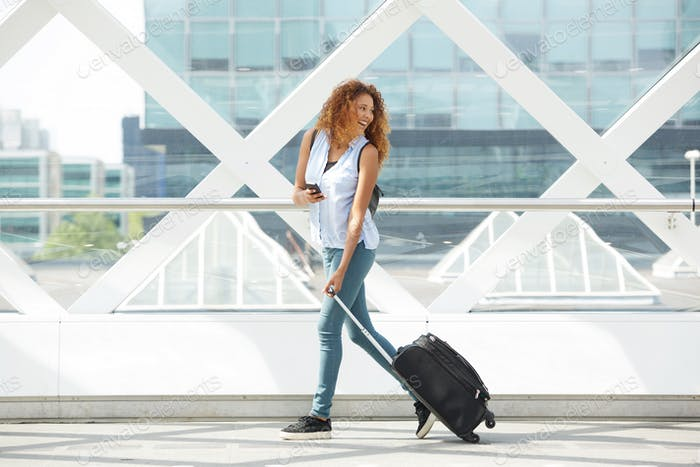 Full length side portrait of happy woman walking on station platform with cellphone and suitcase