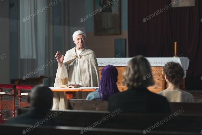 Sacerdote bendiciendo a la gente en la iglesia