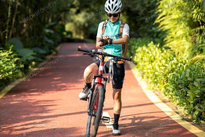 Woman biker set her smartwatch in park