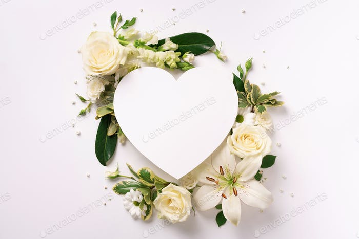 Frame of white flowers, paper heart over light background. Valentines day, Woman day concept. Spring
