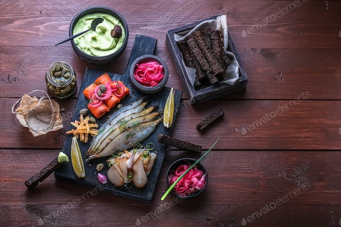 Assorted marinated fish on dark cutting board, copy space