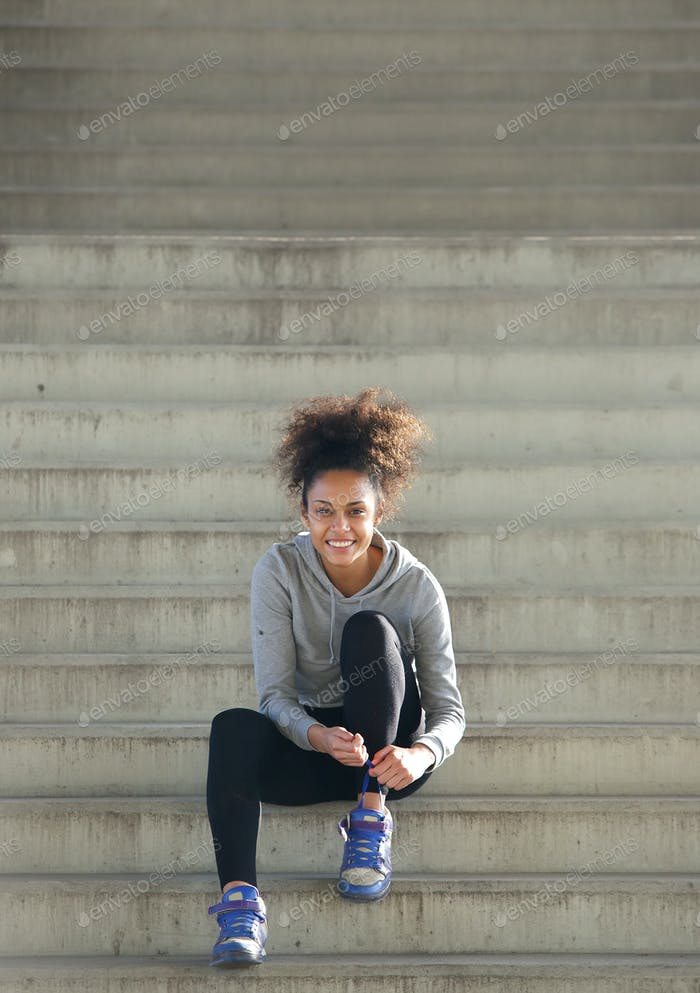 Sporty young woman sitting on steps tying shoe lace