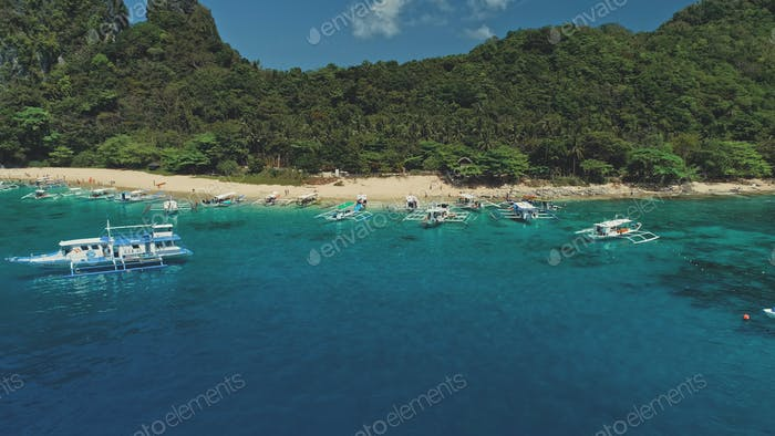 Boats on ocean bay aerial view at sand beach. Tropical jungle forest on mountain island El Nido