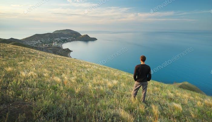 Mann am Rande. Klippe von Berg und Meer.