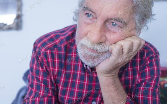Serious and worried portrait of old senior caucasian man at home - people and depression