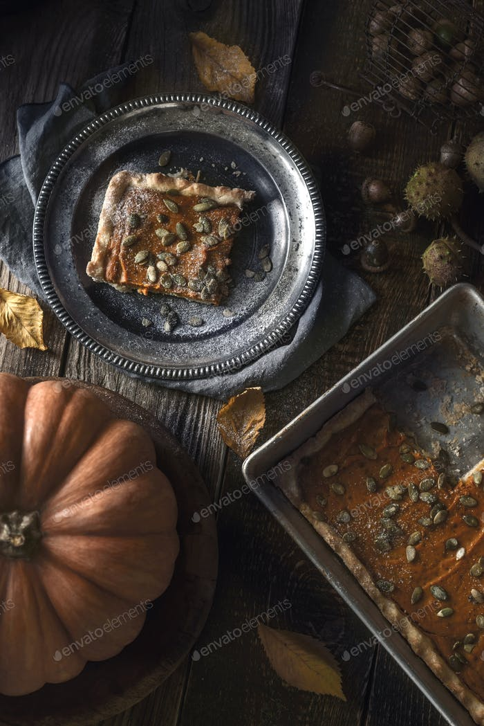 Slice of pumpkin pie on the metal plate on the wooden table with autumn gifts