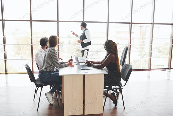 Group of freelancers working in the spacious office with big windows