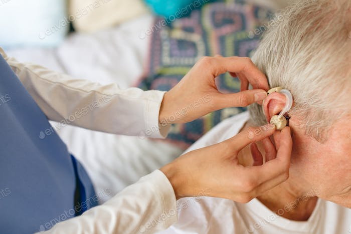 Female nurse applying hearing aid to senior male patient ear at retirement home