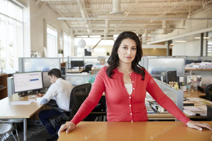 Female architect at a desk in an office smiling to camera