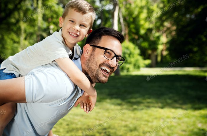 Father carrying his son on back and smiling outdoors