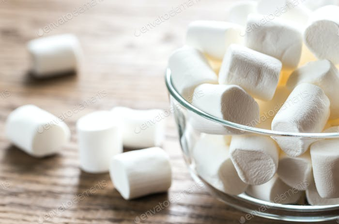 Bowl of marshmallows on the wooden background