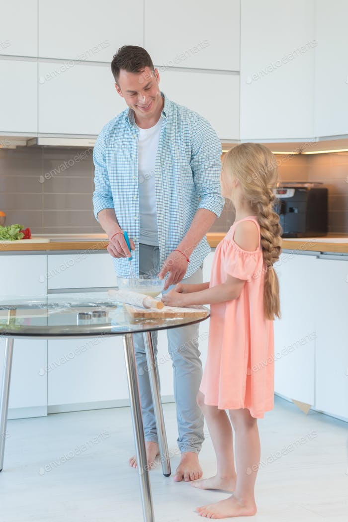 Young father and young daughter preparing in the kitchen