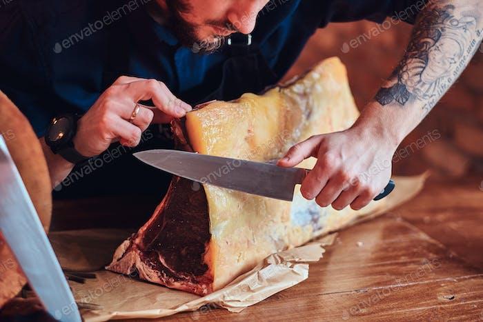 Chefkoch Schneiden exklusives ruckiges Fleisch auf dem Tisch in einer Küche mit Loft-Interieur.