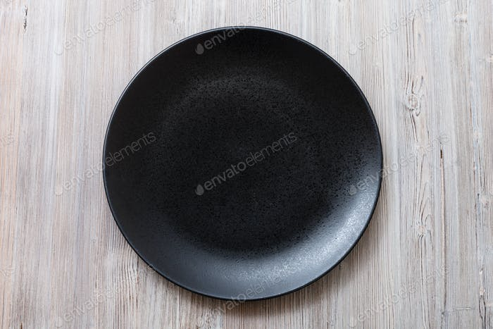 top view of black plate on gray brown table