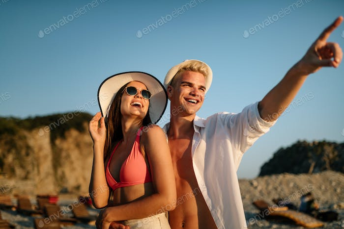 Beautiful young people in love walking. Couple on beach at sunset summer vacation