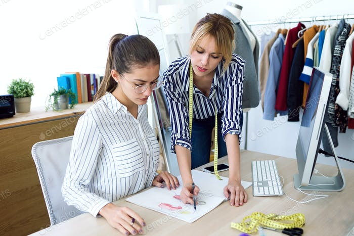 Two young fashion designers deciding on the designs of the new collection of clothes