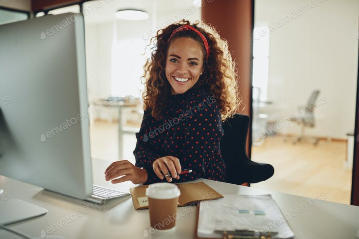Smiling young businesswoman working online at her workstation
