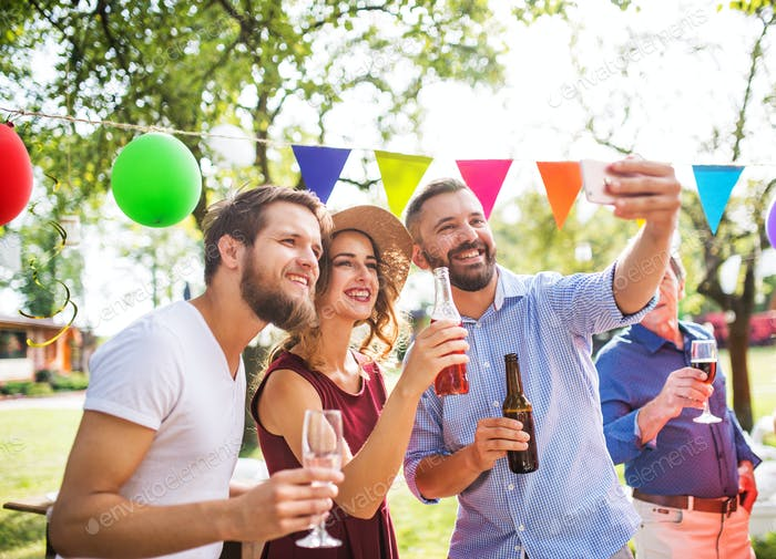 Young people taking selfie at a party outside in the backyard.