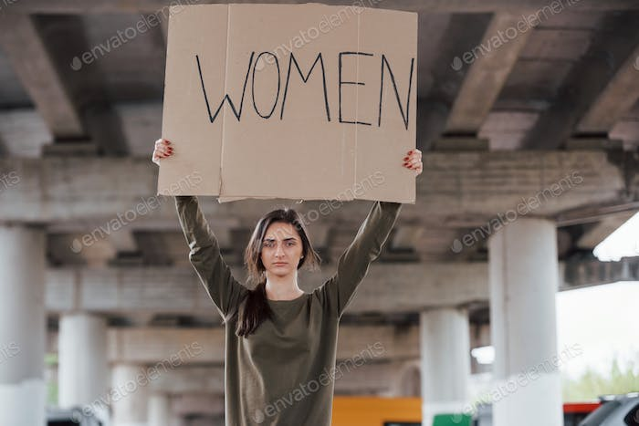 Standing alone. Pretty girl in casual clothes with handmade feminist poster in hands