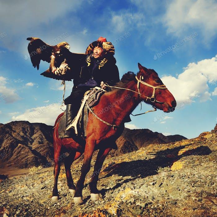 Mongolischer Mann trainiert Adler kasachisch Olgei Western Konzept