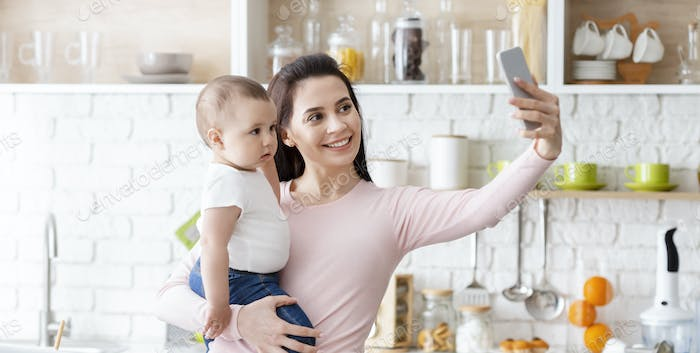 Happy mom taking photo with baby on smartphone at kitchen