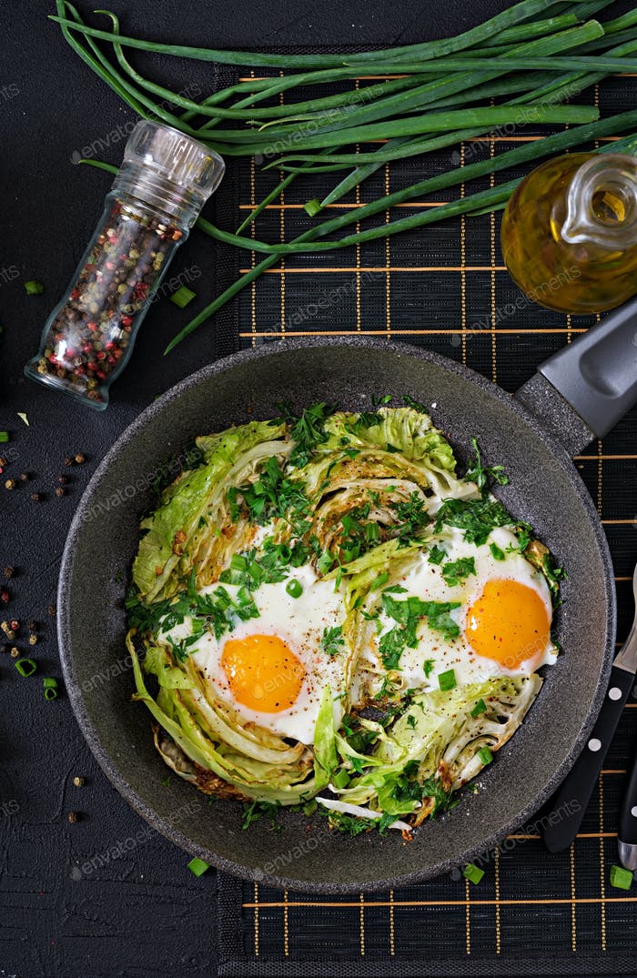 Fried eggs with slices of young cabbage and greens. Nutritious breakfast. Top view. Flat lay