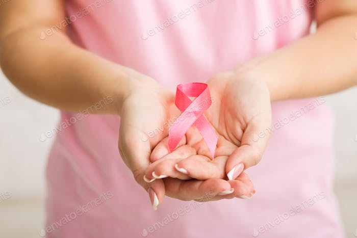 Unrecognizable Girl Holding Pink Ribbon Over White Background, Cropped