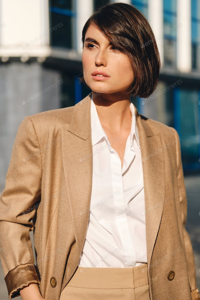 Young confident stylish businesswoman intently looking away on street
